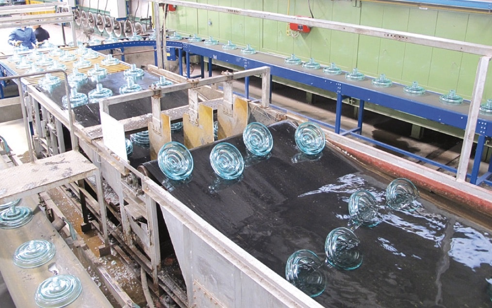After thermal shocks in cold water bath, glass insulators go to quality control inspection. Defective or damaged units are returned for use as cullet on conveyor belt at left Glass Insulator Manufacturing Glass Insulators After thermal shocks in cold water bath glass insulators go to quality control inspection